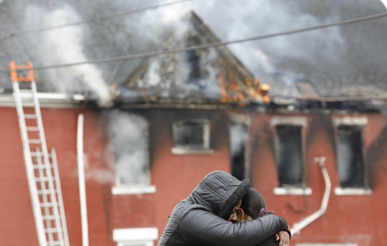 Latasha Colbert comforts Jeishnaly Rivera Tossas of 197 Playter as smoke and flames pour from the building while firefighters work. (Derek Gee/Buffalo News)