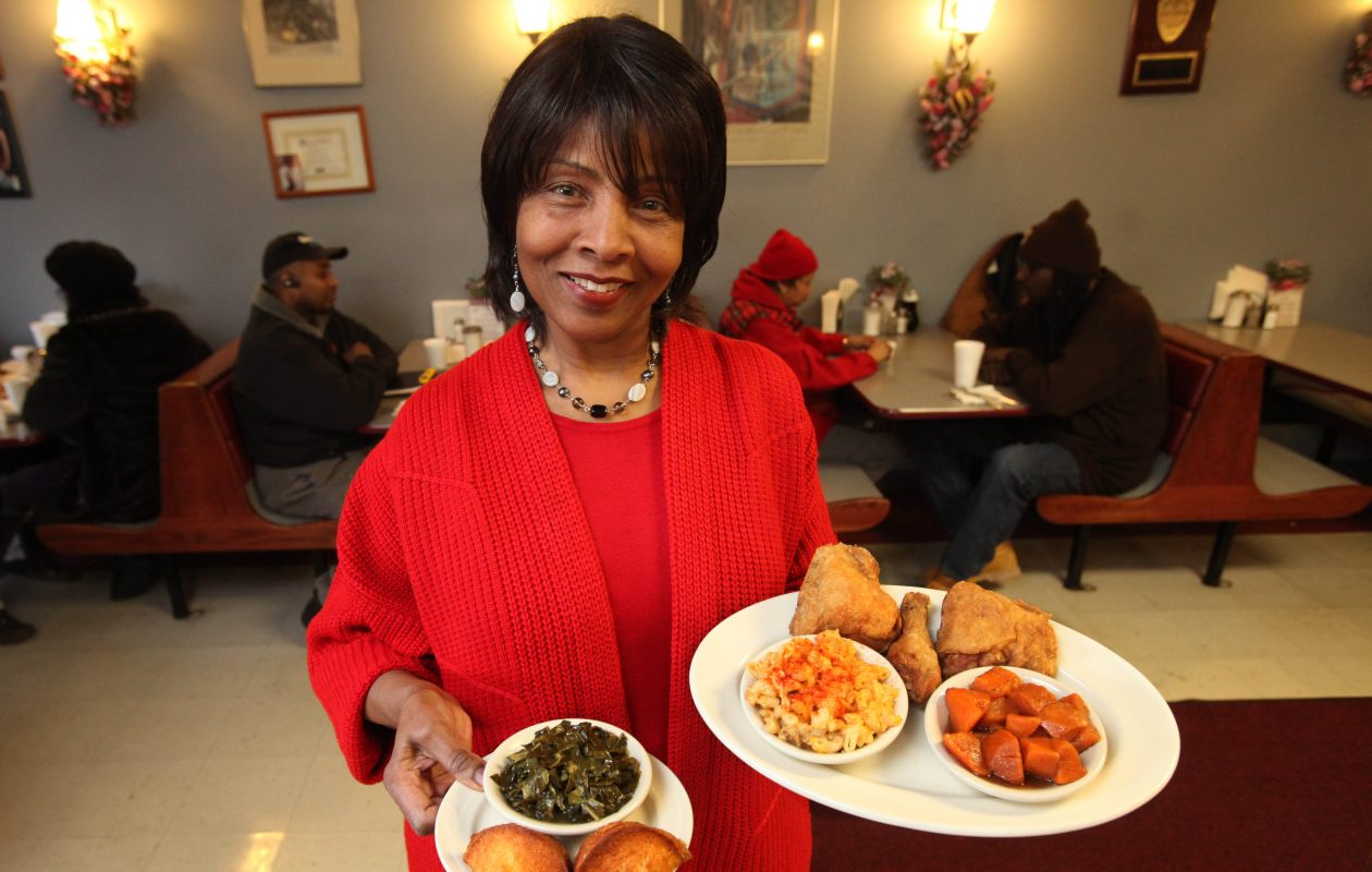 In 2010, Mattie Holt, owner of Mattie's on Fillmore Ave., holds fried chicken, mac and cheese, candied yams, collard green and a corn muffin. (Sharon Cantillon/News file photo)