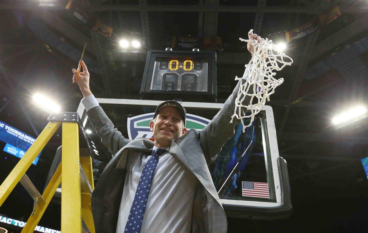 UB coach Nate Oats celebrates as he cuts down the net after the Bulls won the MAC championship. (James P. McCoy/Buffalo News)