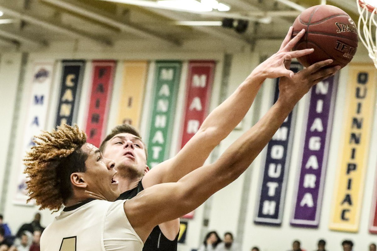 Cardinal O'Hara's Justin Hemphill has his shot blocked by Christopher Stineman of Nichols in the first half of a Manhattan Cup Class B boys basketball final Saturday at Canisius College. (James P. McCoy/The Buffalo News)