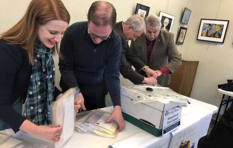 Library director Paula Klocek, town historian Robert Goller, Supervisor James Bach and Councilman Chuck Snyder vacuum-seal time capsule letters. (Samantha Christmann/Buffalo News)