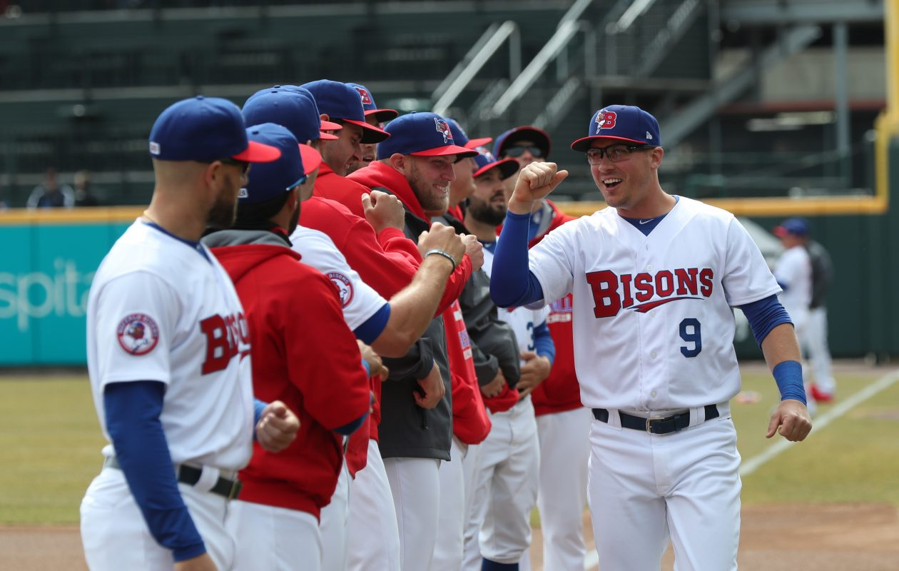 Andy Burns (9) gets high fives from his teammates during pregame introductions on Opening Day. (James P. McCoy/Buffalo News)