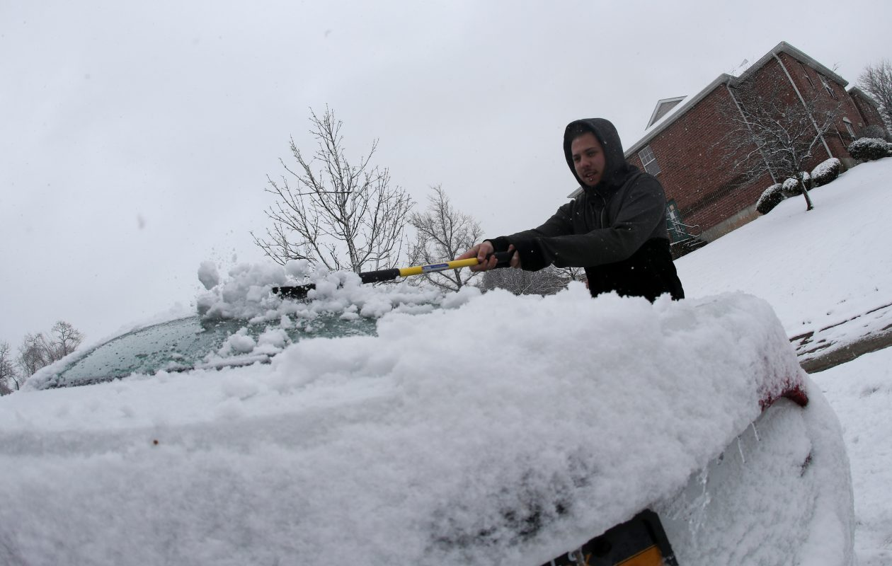 Domenico Brunner  brushes snow off his car  on Eton Lane in Amherst, N.Y., on Sunday, March 31, 2019. Sunday's snow could be the last we see for a while. (James P. McCoy/Buffalo News)