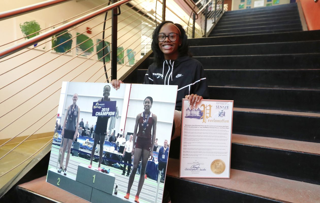Jade Kenner shows off a poster of her stadning at the winner's podium during the state meet  and holds up the proclamation declaring April 5 as Jada Kenner Day during a ceremony at Tapestry Charter School on Friday. (James P. McCoy/Buffalo News)