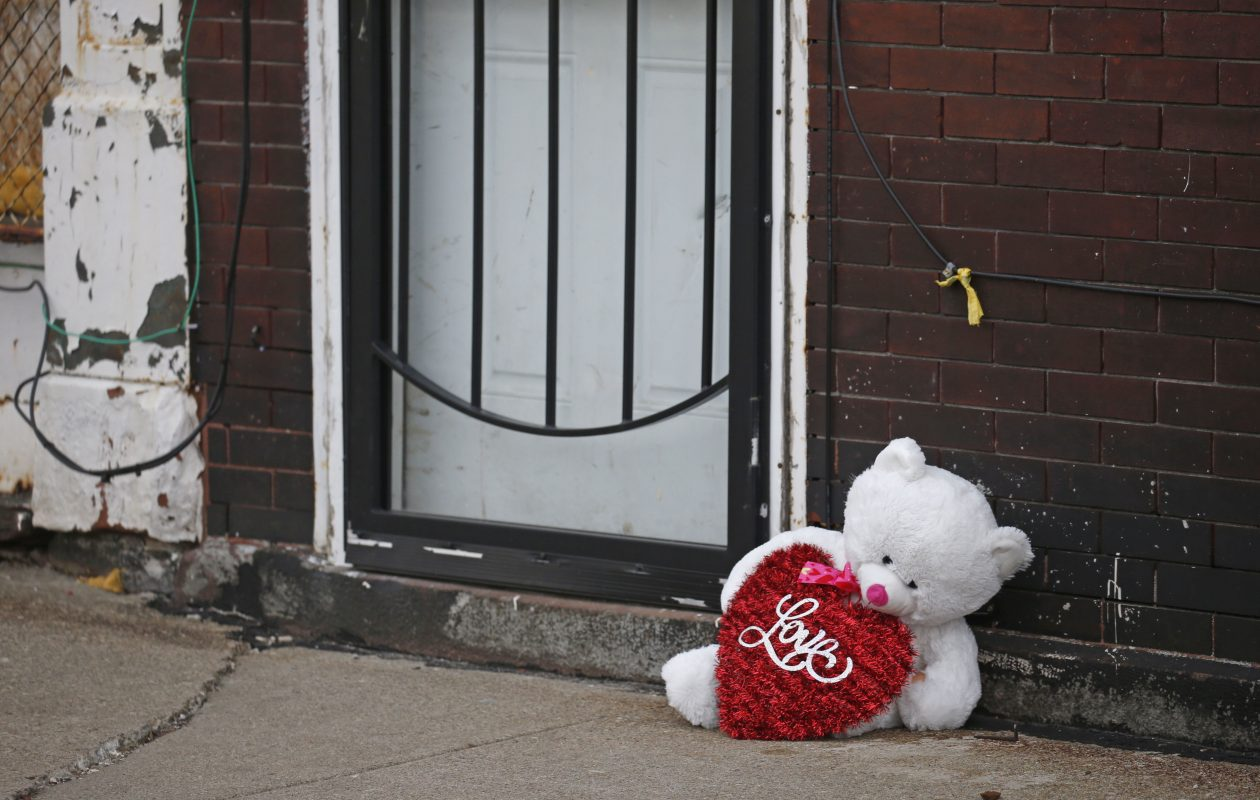 A teddy bear sits outside of the entrance to a building on William Street where a 12-year-old boy was struck in the head by a stray bullet. (Robert Kirkham/Buffalo News)