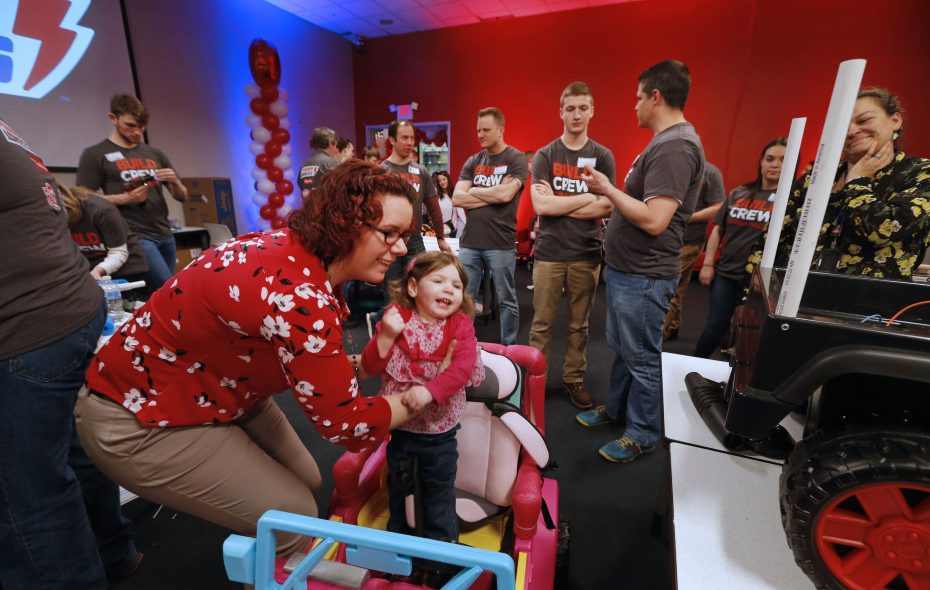 Camie Jarrell, of West Seneca, places her daughter Cadence, 2, into her new car to take a first ride. As part of the GoBabyGo program, Fisher-Price employees and Technical Education students from Central Connecticut University teamed up to modify customized Power Wheels for eight Western New York children with special needs and mobility requirements.. (Robert Kirkham/Buffalo News)