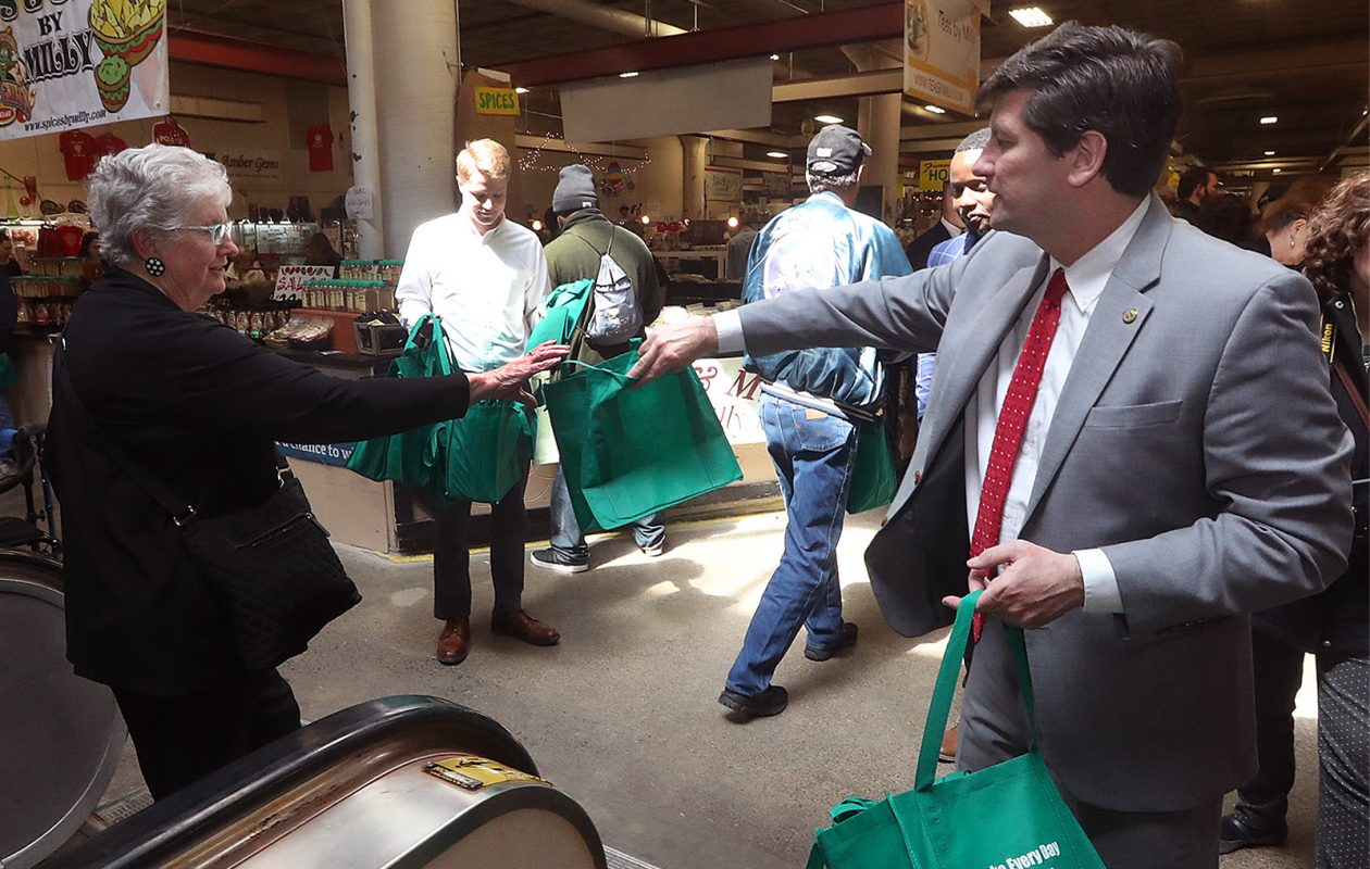 Erie County Executive Mark Poloncarz, who supports a 5-cent fee on paper bags, gives away free reusable bags at the Broadway Market, in Buffalo, on Wednesday, April 17, 2019.   (John Hickey/Buffalo News)
