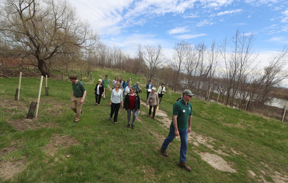 A group walks with Nancy Smith, executive director of the WNY Land Conservancy, at Red Jacket Riverfront Park on Thursday, April 25, 2019. (John Hickey/Buffalo News)
