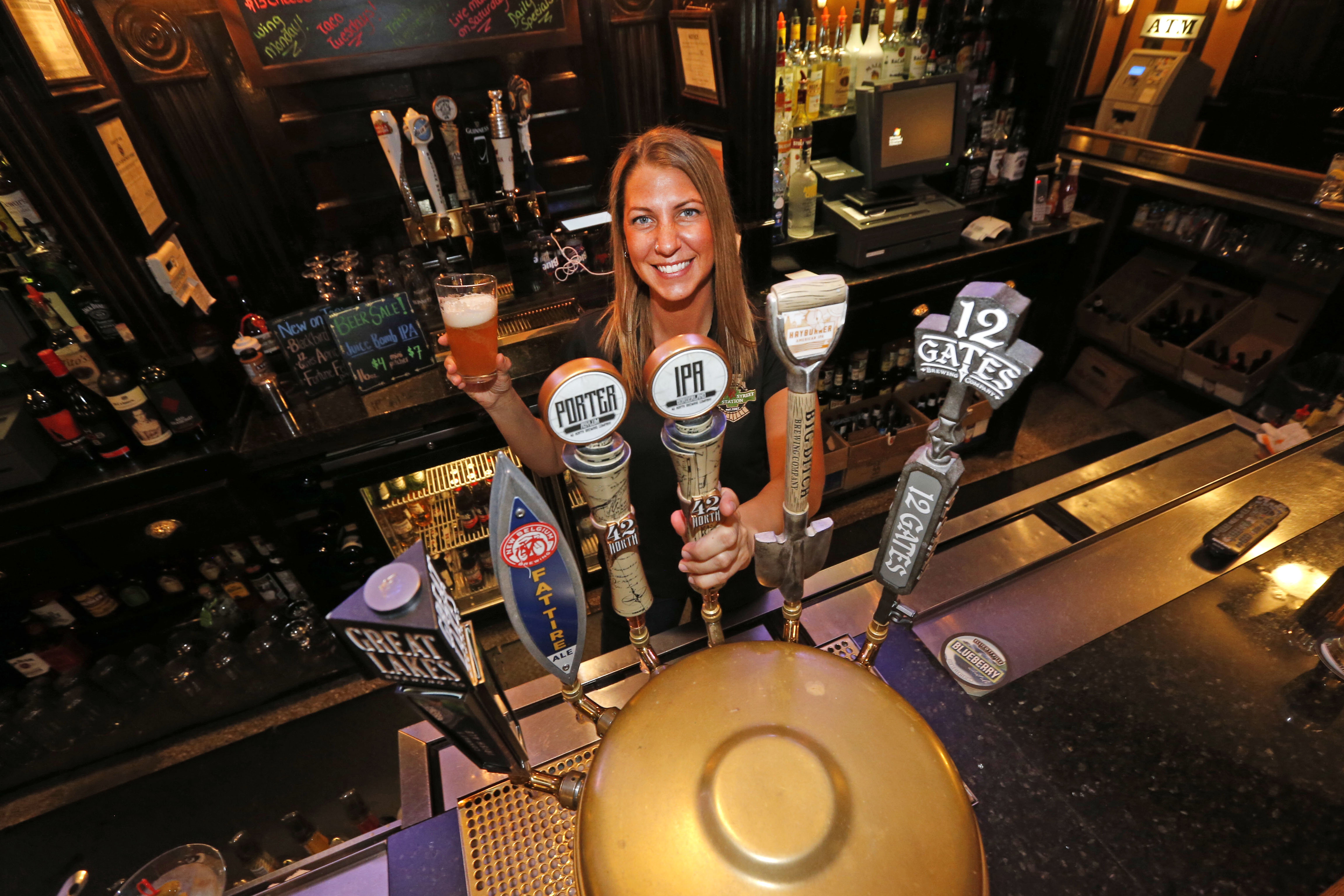 Bartender Candice Kulikowski pours a 42 North IPA at Riley Street Station in East Aurora. (Robert Kirkham/Buffalo News)