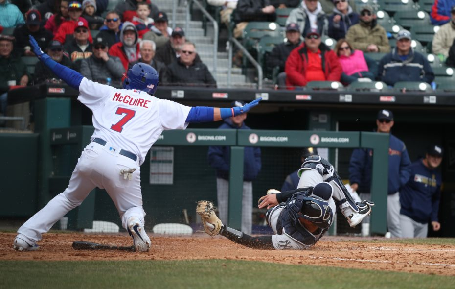 Buffalo Bisons catcher Reese McGuire slides safe into home plate under the tag of Scranton/Wilkes-Barre RailRiders catcher Kyle Higashioka the third inning of opening day at Sahlen Field on April 4, 2019.  (James P. McCoy/Buffalo News)