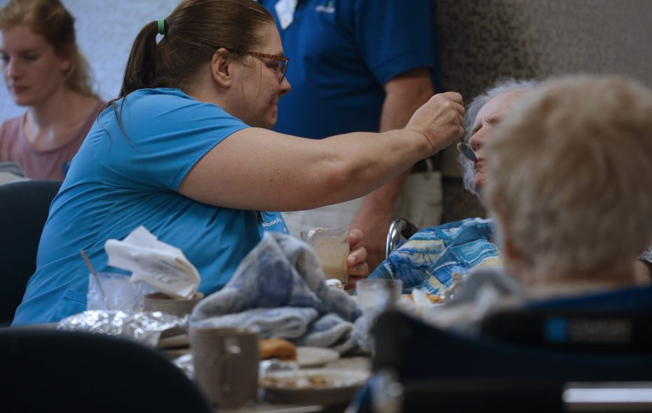 Certified nursing assistant Carolyn Delzer feeds a resident at Absolut Center for Nursing and Rehabilitation at Aurora Park, a nursing home in East Aurora. New York State's Health Department will study in 2019 whether to adopt minimum staffing requirements at hospitals and nursing homes. (Robert Kirkham/News file photo)