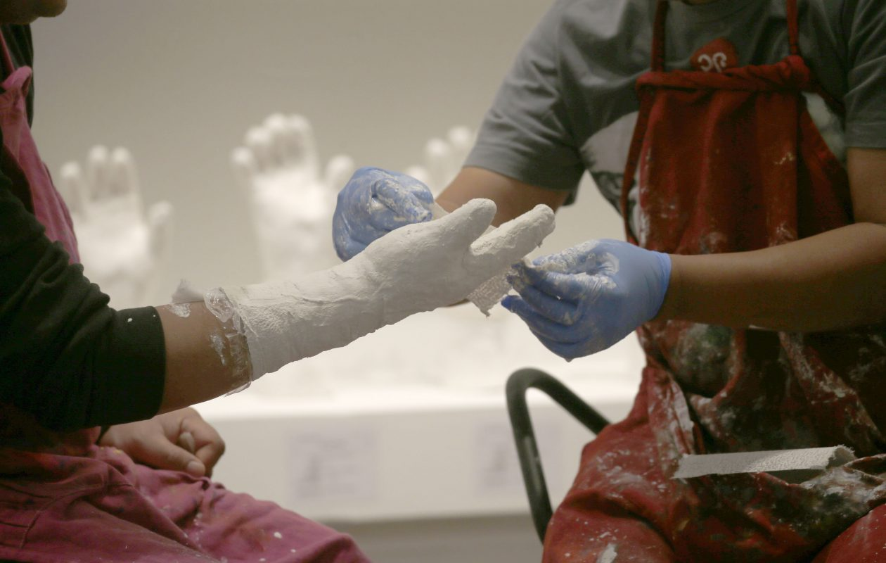 Htein Lin makes a plaster cast of the right hand of Aung Myat Thu, a fellow former political prisoner from Burma, at the Albright-Knox Art Gallery on Sunday. Lin makes casts of former prisoners' hands, and includes them in his ongoing 'A Show of Hands' project, part of which is on view in the gallery. (Robert Kirkham/Buffalo News)