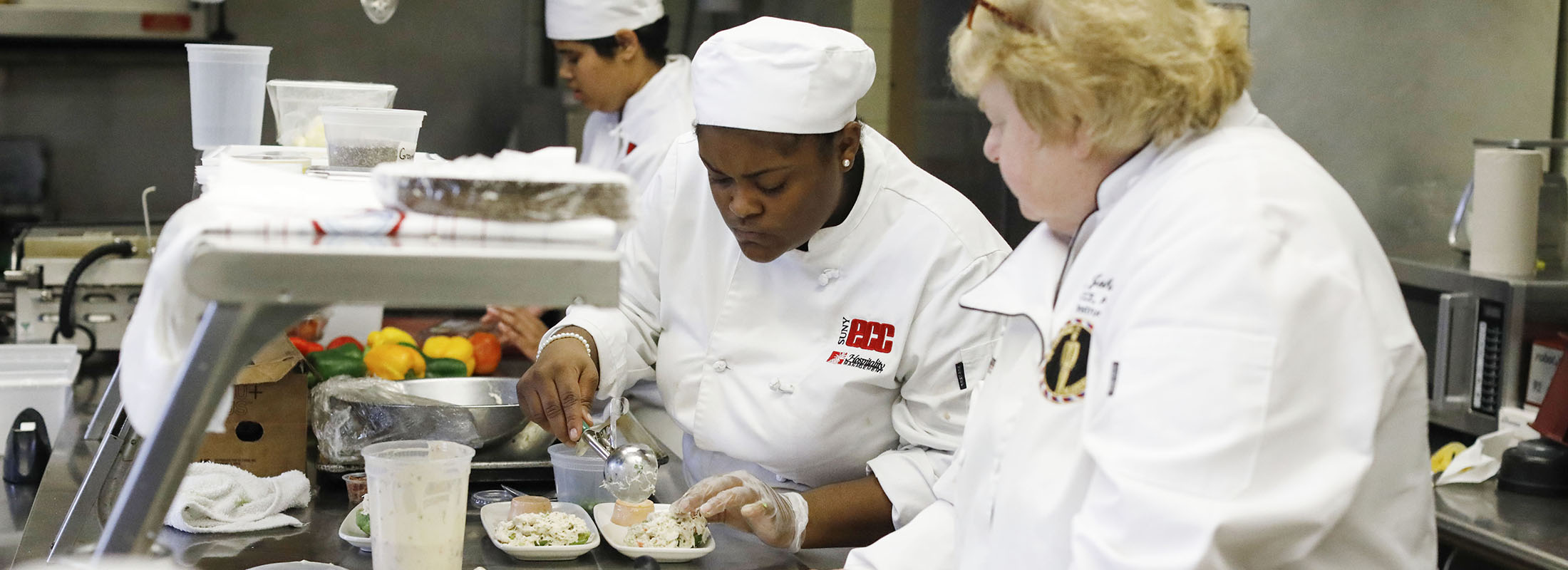 Erie Community College culinary student Alicia Barker-Smith creates a dish as associate professor Dorothy Johnston watches in the kitchen at the E.M. Statler Dining Room in ECC City Campus. (Derek Gee/Buffalo News)