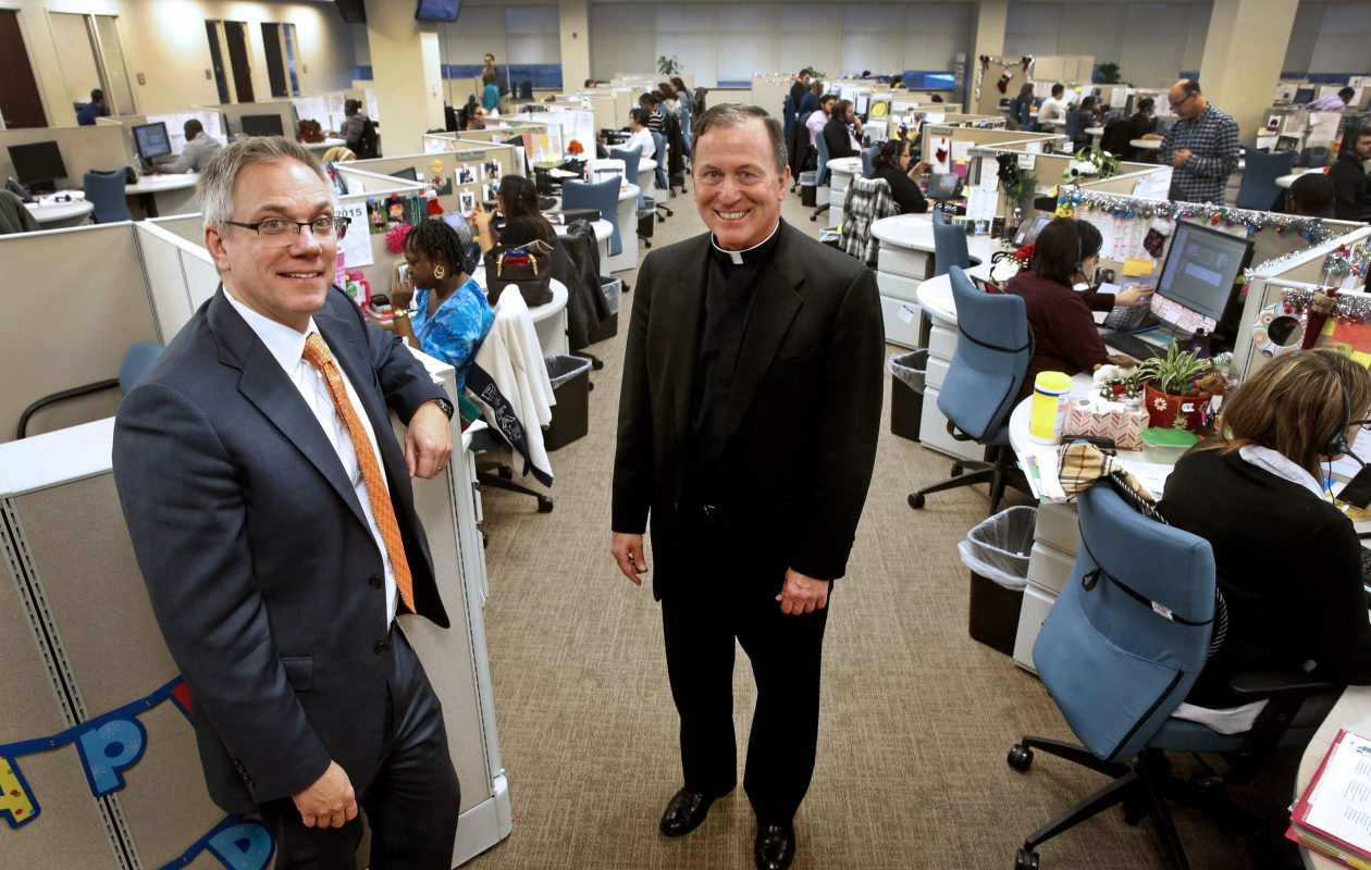 David Thomas, left, now president and CEO of Fidelis Care, and the Rev. Patrick J. Frawley, right, Thomas' predecessor, during a 2015 visit to the health insurer's offices in Getzville, where Fidelis Care may expand again.  (Robert Kirkham/Buffalo News file photo)