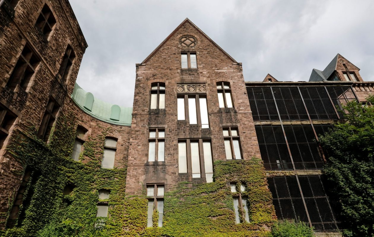 Ivy covers a portion of the east wing at the Richardson Olmsted Campus. At left is the eastern edge of the Hotel Henry. (Derek Gee/Buffalo News)