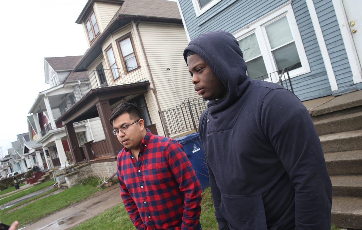 Custer Street neighbors Adam Rodriguez, left, and Lavontae Armwood talk about what they witnessed Thursday night when a student was brought out between houses and police and rescue personnel worked on the passed-out male in the driveway. (John Hickey/Buffalo News)