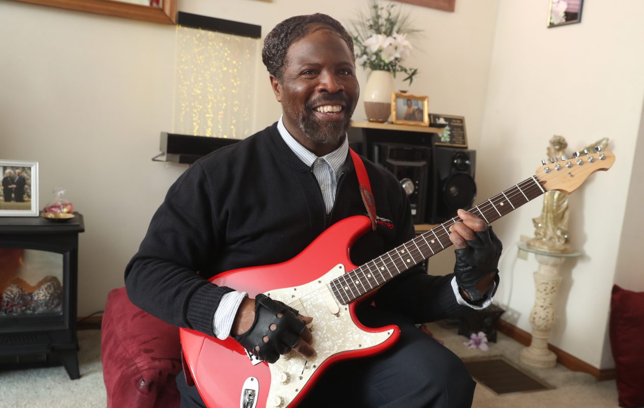 Washington H. Lewis plays the guitar at his Buffalo home on March 8, 2019. (John Hickey/Buffalo News)