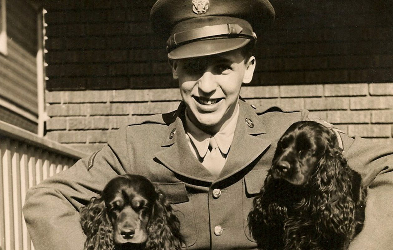 Vince Rogers Jr., on a visit with his parents in Snyder during World War II, embraces 'the girls,' Melody and Music, the family dogs. (Image courtesy of March Field Air Museum)