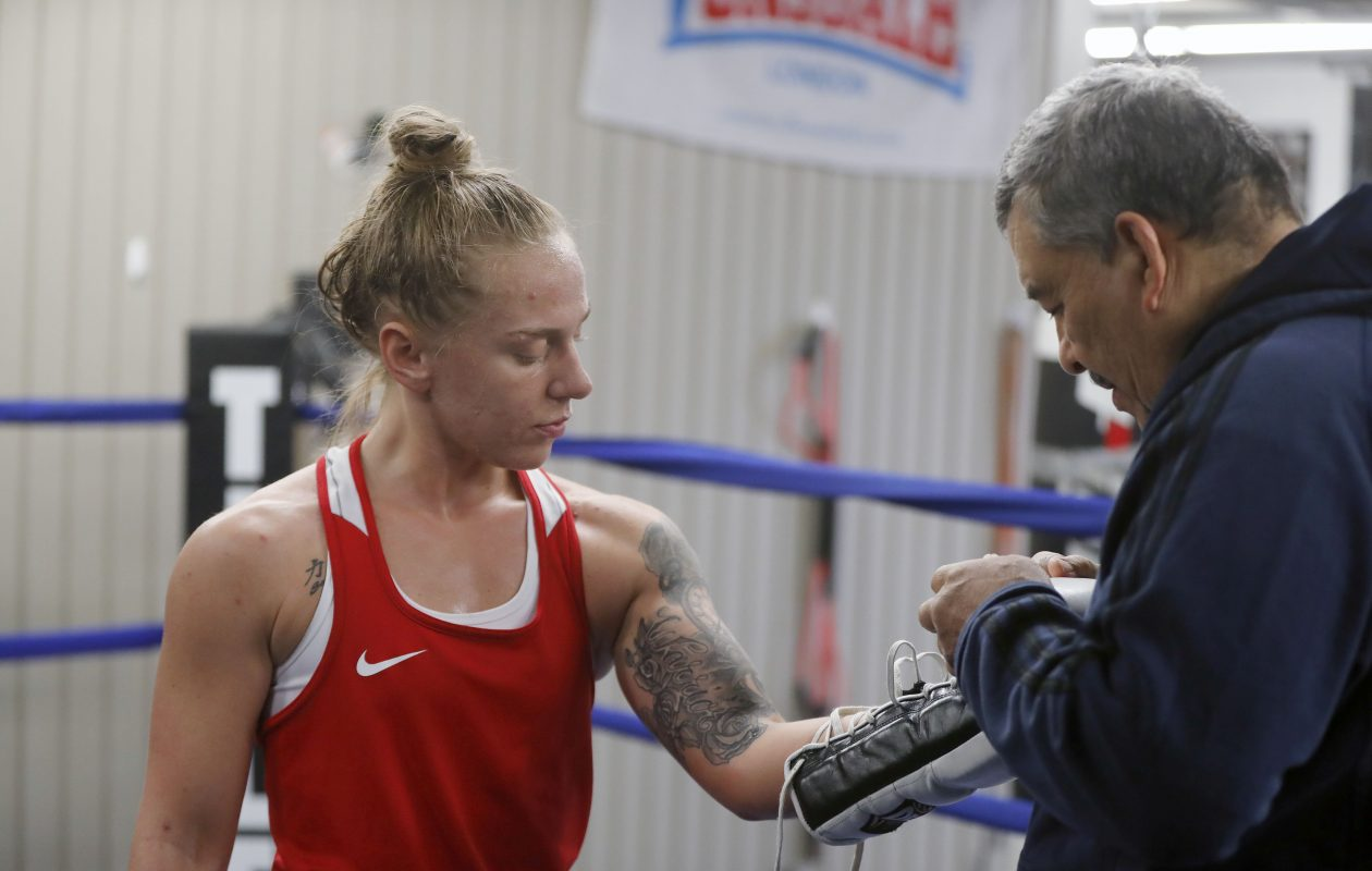 Boxer Mikiah Kreps gets help putting on some boxing gloves by her trainer Hector Alejandro during her workout at the Gonzalez Boxing Club in Niagara Falls Tuesday, April 30, 2019.      (Mark Mulville/Buffalo News)