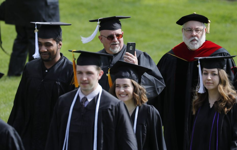 Robert Suda snaps a photo as he and Adonte Buster, left, march in the Houghton College graduation in Houghton on Saturday, May 11, 2019. The two are are the first graduates of the Houghton at Hope House program that is offered for parolees. (Mark Mulville/Buffalo News)