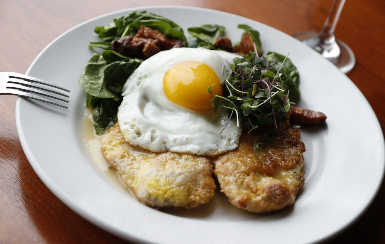 At Winfield's Pub, pork cutlet Francaise is a local pork cutlet, egg-dipped and pan-fried with creamy lemon butter white wine sauce, topped with a fried egg, on a bed of spinach with bacon vinaigrette. (Sharon Cantillon/Buffalo News)