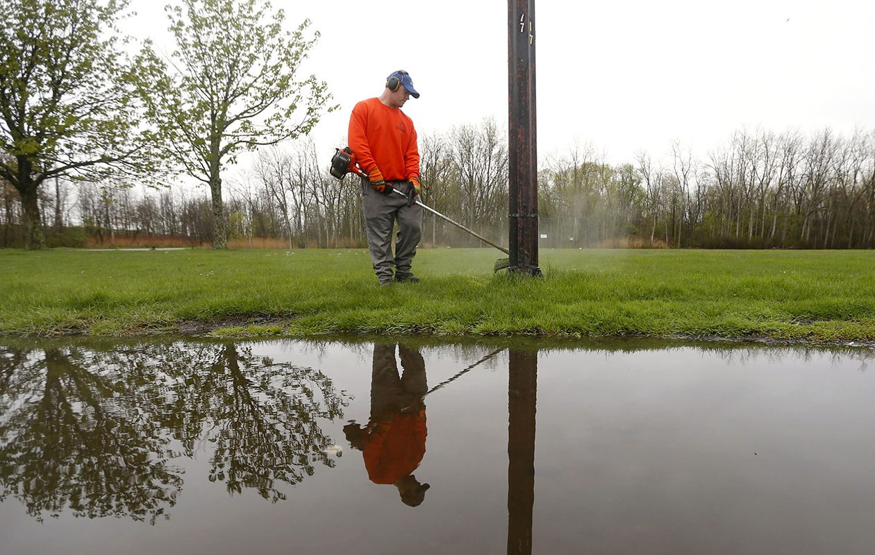Eric Fray trims the grass around a light pole on May 13, a clear, if overcast, day in Buffalo. (Mark Mulville/Buffalo News)