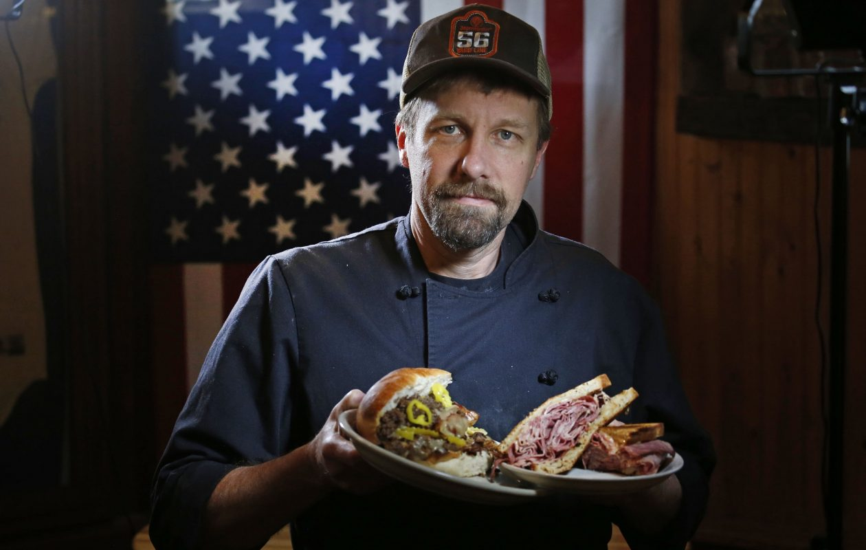 Brawler's manager Tom Ryan holds a steak-and-egg sandwich, left, as well as The Knuckle, a specialty sandwich. (Robert Kirkham/Buffalo News)