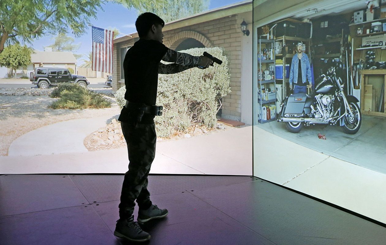 Bodwin Kwanda takes a turn in the VirTra Police Simulator, which gives students a chance to see how they would react as police officers in different life-and-death situations. (Robert Kirkham/Buffalo News)