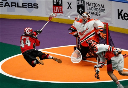 Dane Dobbie scored three second-half goals and the Calgary Roughnecks withstood a late rally to defeat the Buffalo Bandits, 10-7, in the first game of the best-of-three National Lacrosse League finals on Saturday night at KeyBank Center.