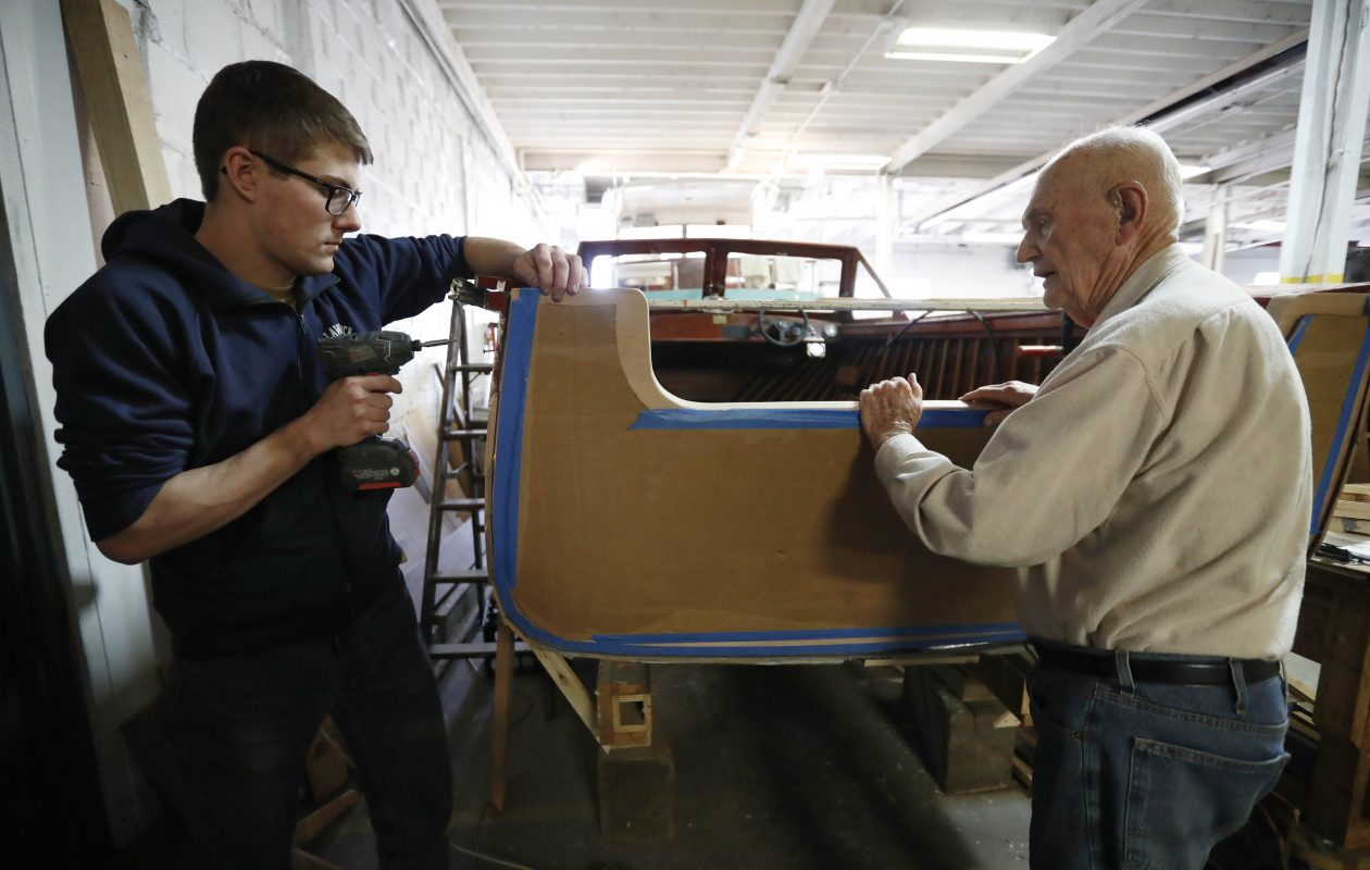 Adam Curcio, left, was given a 1962 Grady-White Hatteras after the death of a close family friend. It was in rough condition, and Jim Holler has become his mentor and teacher in repairing it. (Sharon Cantillon/Buffalo News)