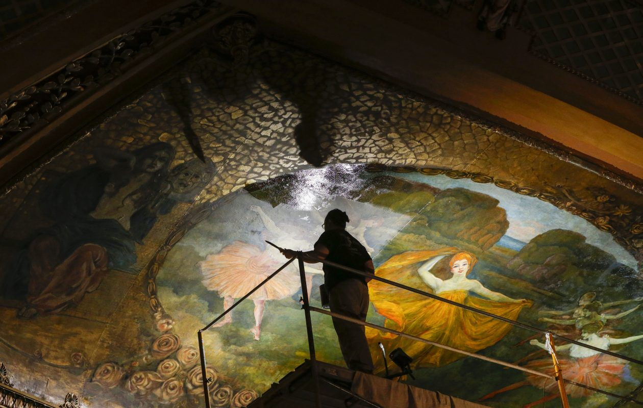 Cristiano Pereira brushes  a coat of varnish over the restored fresco above the stage in the North Park Theatre. (Derek Gee/Buffalo News)
