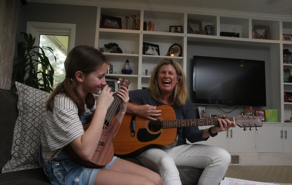 "Brigid Maloney, co-leader with the Lippes Mathias Wexler Friedman firm's Health Law Practice, plays guitar and sings with her daughter, Kate, 9, at their home in East Aurora, ""We want to raise kids that are healthy, kind, open-minded and academically conscientious. Everything has to feed into that,"" she says. (John Hickey/Buffalo News)"