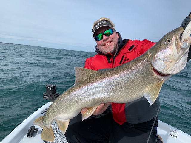 """Mark Davis of South Carolina, host of """"Big Water Adventure"""" TV Show, hoists up one of the first fish of the week - a big Lake Ontario lake trout - to kick off the Niagara Outdoor Media event held May 4-11. (Photo by Frank Campbell)"""