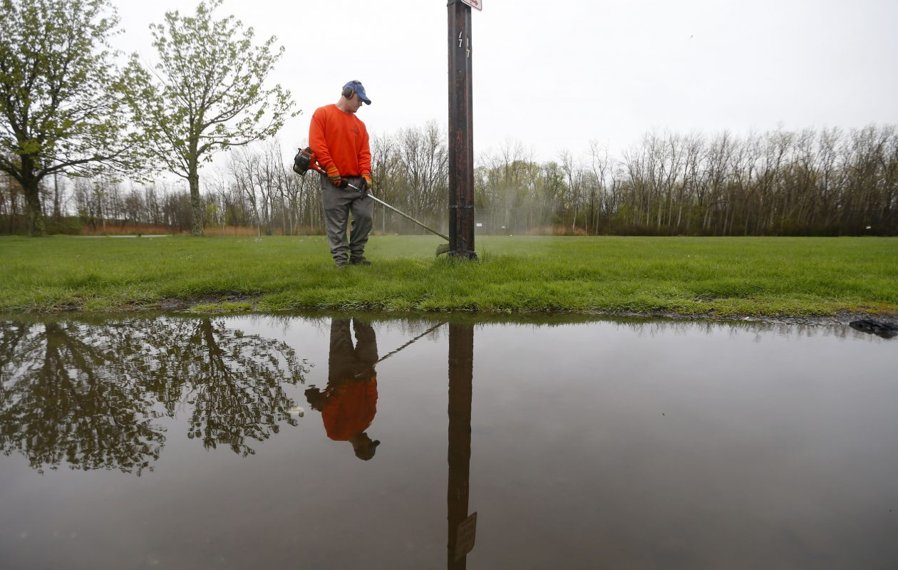 Eric Fray trims the grass around a light pole in South Park. (Mark Mulville/Buffalo News)