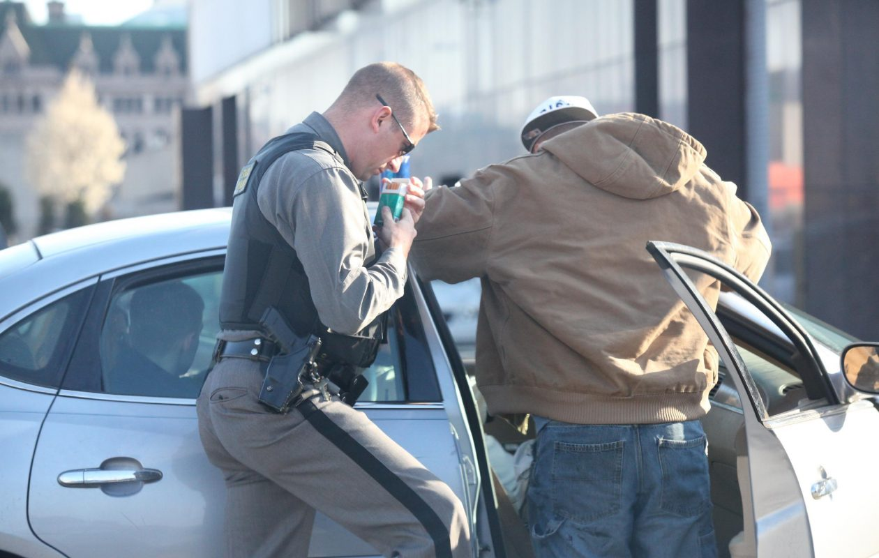 A New York State trooper  searches a car and its four passengers on the corner of Oak and WIlliam streets. (Harry Scull Jr./News file photo)