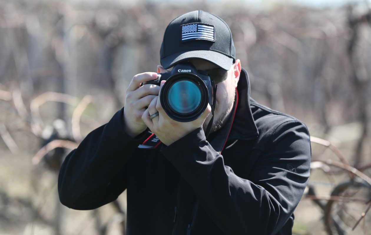 Christopher Veltri, a veteran, learns how to use his new camera during a photo shoot at a local vineyard near in Angola in April. (James P. McCoy/Buffalo News)