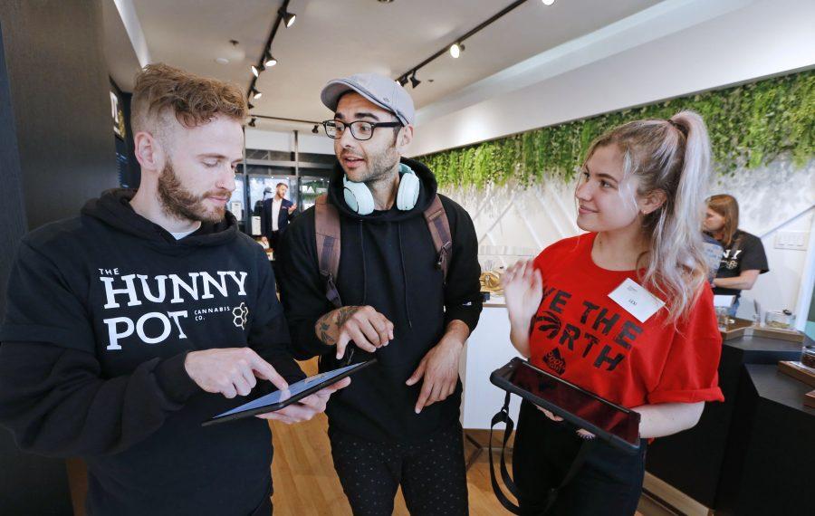 """Bud tenders"" Craig McCann, left, and Lexi Medici, right, talk customer Adam Ash through the shopping and buying process at the Hunny Pot in Toronto. (Robert Kirkham/Buffalo News)"