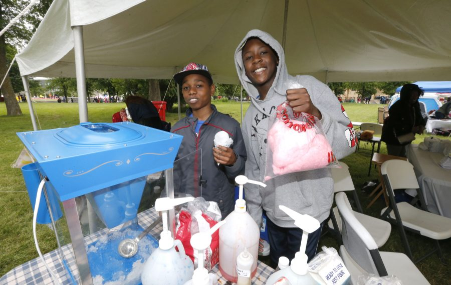 """Djibril Horsford, left, and Staz Chiddick, the 11-year-old owners of SD Smiley Face Concession, sell snow cones and cotton candy at the Juneteenth Festival, using the skills they honed during a """"pitch"""" competition for young entrepreneurs. (Robert Kirkham/Buffalo News)"""