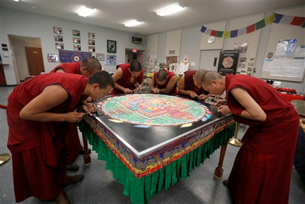 Tibetan monks of the Drepung Loseling Monastery create a sand mandala in the fire hall of the Lily Dale Assembly part of the season-opening festivities for the spiritualist community in Chautauqua County. The mandala is one of the tools the monks use to re-consecrate the earth and all its inhabitants. A Buddhist mandala is envisaged as a sacred space.