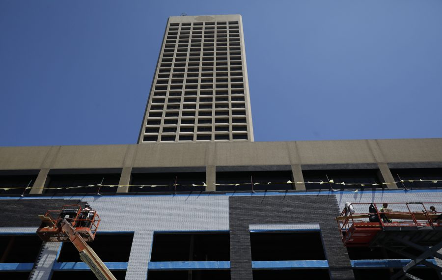 Crews work on the facade as construction work continues on a newly framed section on the west side of One Seneca Tower on Pearl Street on Wednesday. (Derek Gee/Buffalo News)