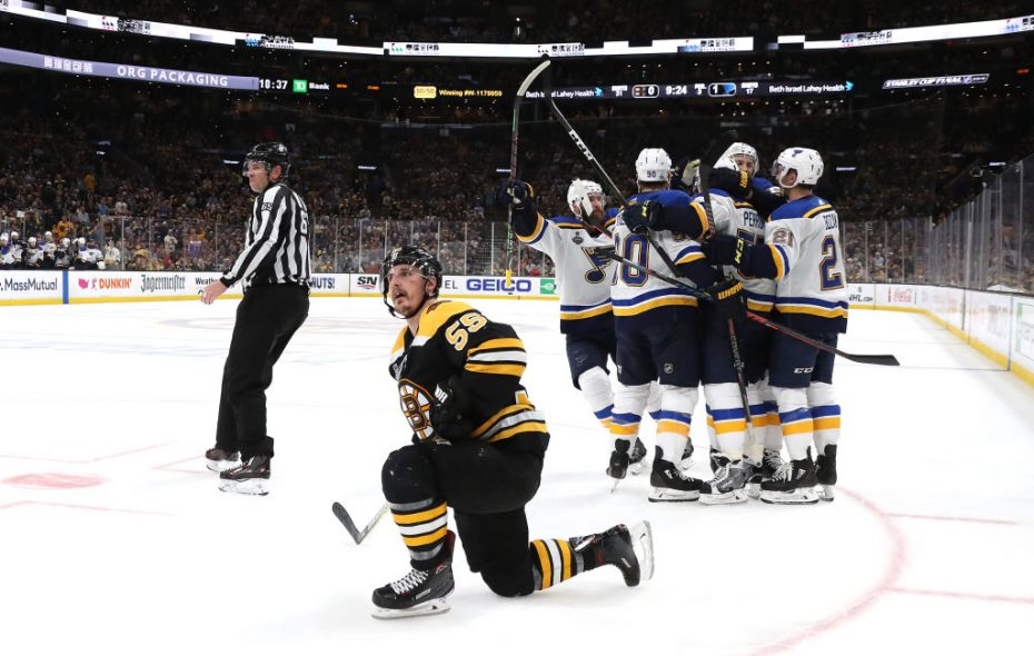 The Blues celebrate David Perron's third-period goal in Game 5 as Boston's Noel Acciari is dismayed after he was taken out of the play by St. Louis center Tyler Bozak. (Getty Images)