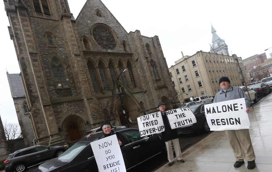 Former Catholic priest James Faluszczak, on right, protests on April 14, 2019 in Buffalo about how Bishop Richard J. Malone has handled clergy sexual abuse allegations. Protesting with him are Judith Burns-Quinn and Robert Hoatson. (John Hickey/News file photo)
