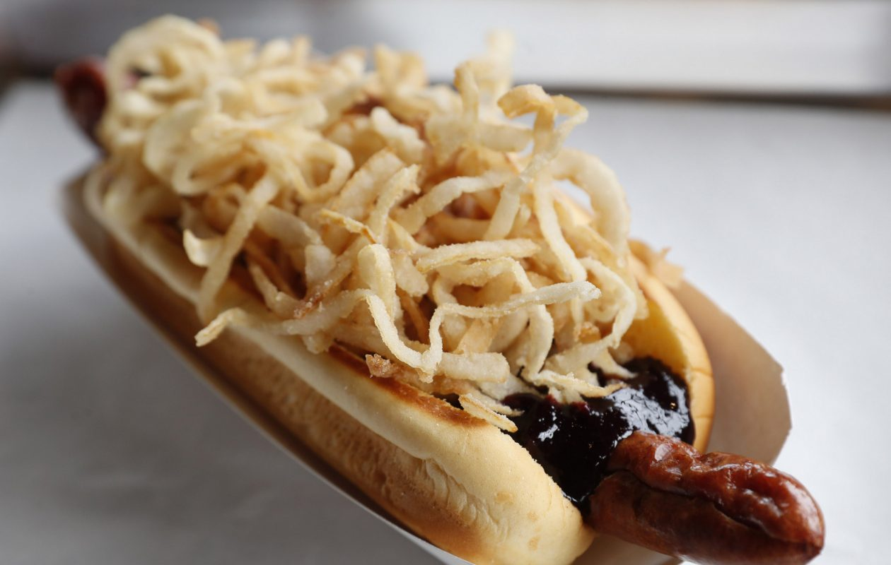 Frank Gourmet Hot Dogs' Violet Beauregarde is topped with blueberry barbecue sauce, cheddar cheese and onion crunch. (Sharon Cantillon/Buffalo News)
