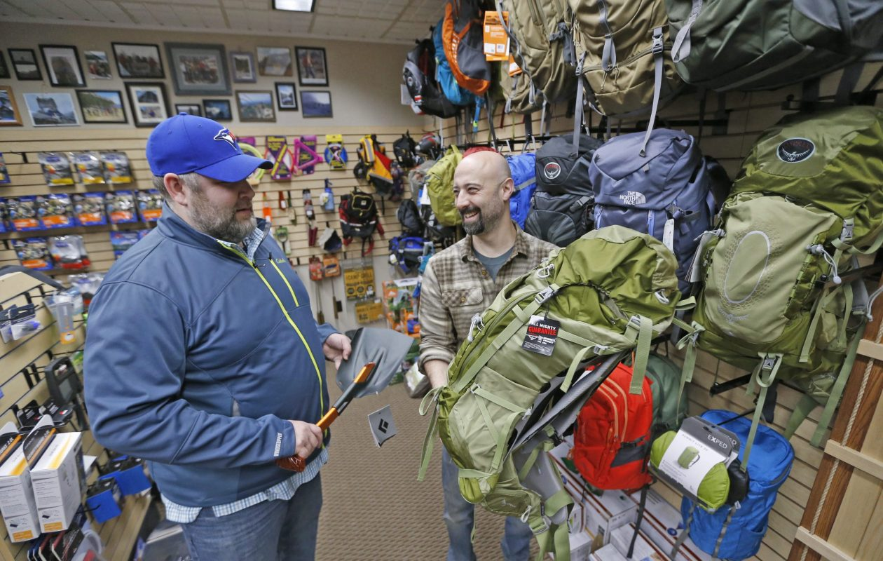 Gear for Adventure store owner Kevin Beckwith, right, shows customer Darren Lehman, left, some products at his Hamburg store. (Robert Kirkham/Buffalo News)