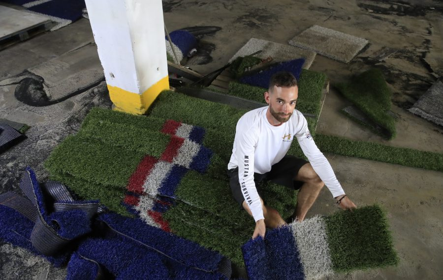 Pat Brady sits with some of the 40,000 square feet of artificial turf that he bought at auction that the Buffalo Bills used from the 2011-2018 seasons. (Harry Scull Jr./Buffalo News)