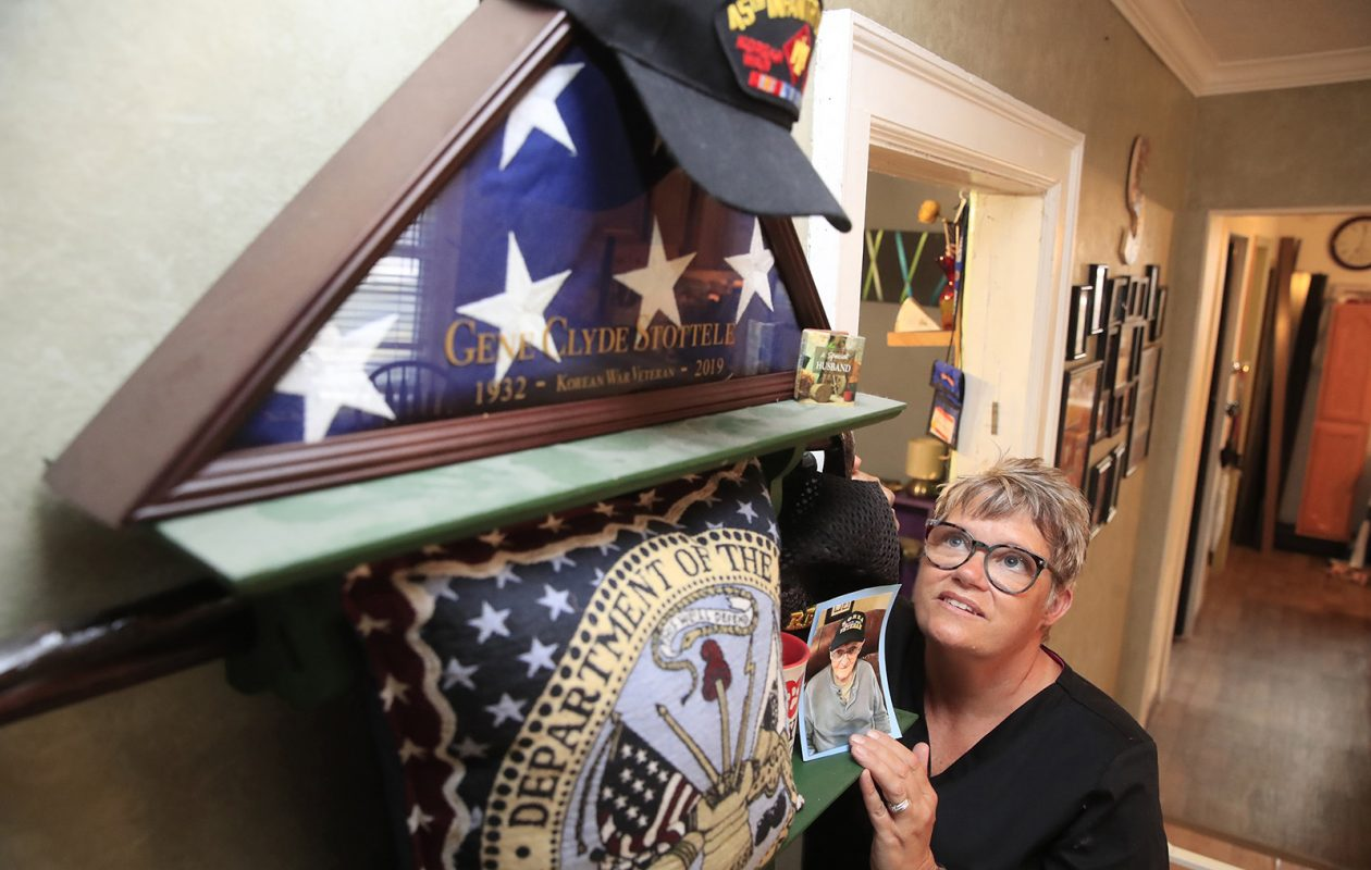 Nancy Kerr looks at mementos from her father, Gene Clyde Stottele, a decorated Korean War veteran. Stottele's remains are among many awaiting burial in a long-delayed military cemetery in Pembroke. The excuses for the delays no longer carry weight. (Harry Scull Jr./Buffalo News)