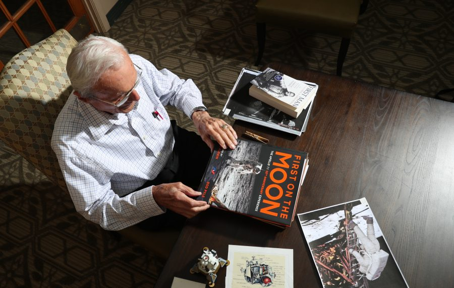 At 97, William Swenson studies old photos, badges, and books that catalog a process in which he was intimately involved as an engineer at Bell Aerosystems. (James P. McCoy/Buffalo News)