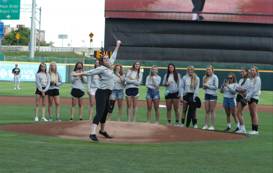 With her Class A state champion softball teammates behind her, Williamsville East pitcher Summer Clark throws out the ceremonial first pitch before Monday's Buffalo Bisons game with Charlotte at Sahlen Field. (James P. McCoy/Buffalo News)