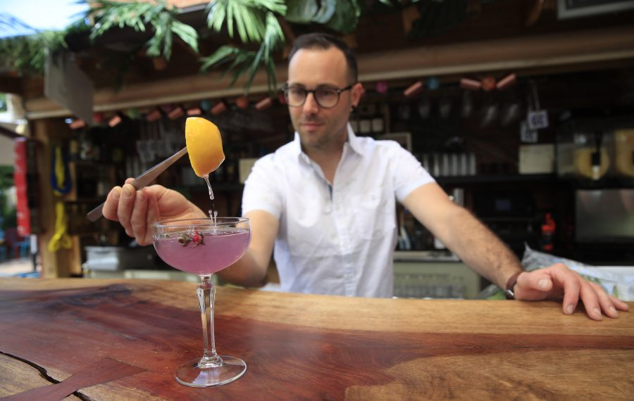 Hydraulic Hearth bar manager Adam Rath lightens the color of the Hydrangea by pouring lemon juice from a hollowed-out lemon into the cocktail. (Harry Scull Jr./Buffalo News)