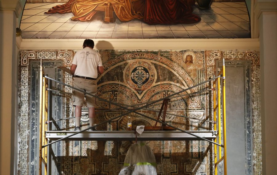Century-old artwork by a Danish master was discovered in Our Lady of Charity Parish in South Buffalo. Restoration expert Henry Swiatek has been working on the project since spring and will finish in the fall. Stephen Rovner is shown working on the St. Joseph side altar. (Sharon Cantillon/Buffalo News)